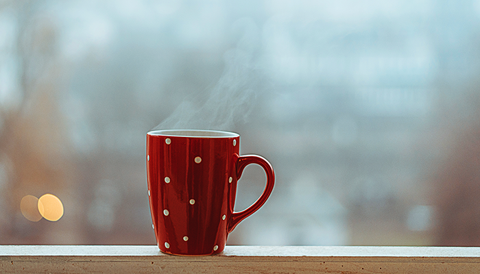 Steaming cup of tea in red spotted mug